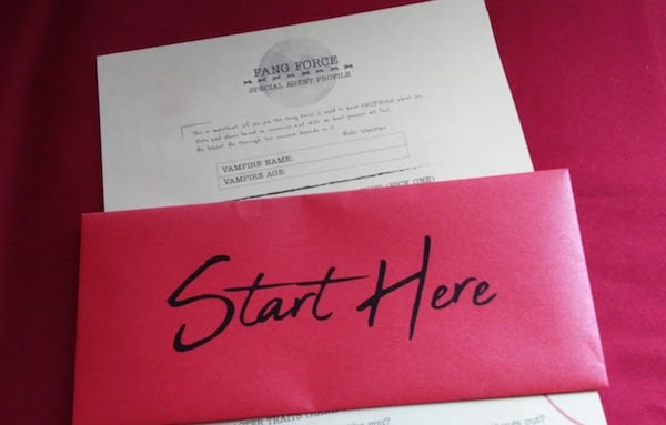 "An envelope reading ""Start Here"" accompanied by a Fang Force Special Agent Profile sheet."