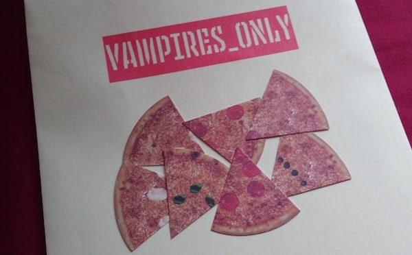 "A dossier reading ""Vampires Only"" with some game pieces shaped like pizza slices."