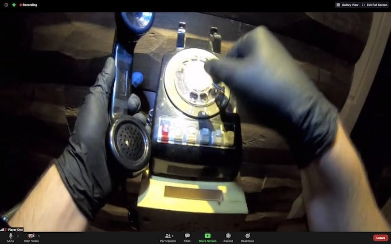 A pair of hands in black latex gloves manipulating an old rotary phone.