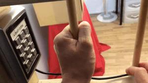 Hands holding bars beside a digital keypad.