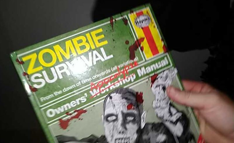 First person of a hand holding a Zombie Survival guidebook.