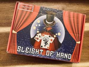 Box art for Sleight of Hand, depicting an empty magician's cape with a floating hat, wand, and cards as if an invisible spirit were holding them.