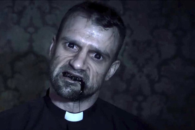 A posessed priest with black fluid flowing from his mouth and dead eyes.