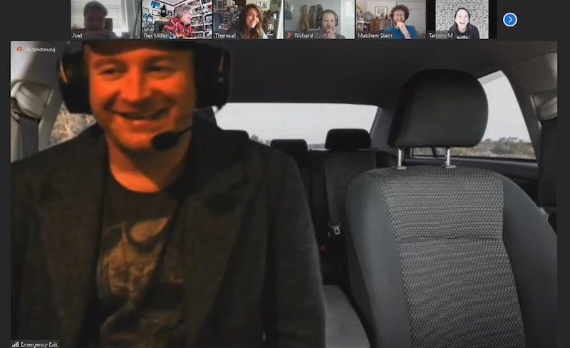 A person in a headset behind the wheel of a car as seen over Zoom.