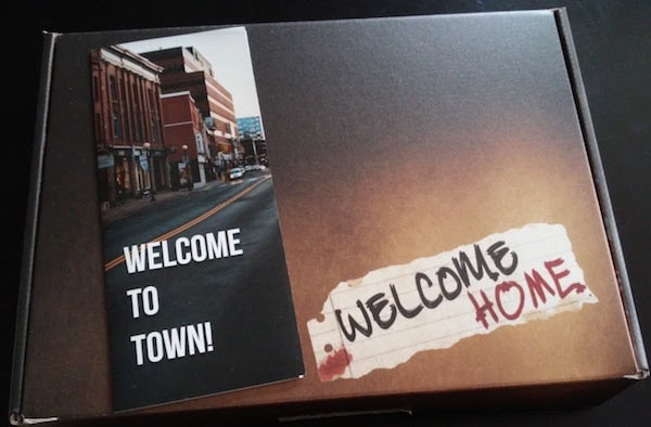 "The closed game box, marked ""Welcome Home,"" with a pamphlet reading ""Welcome to Town!"""
