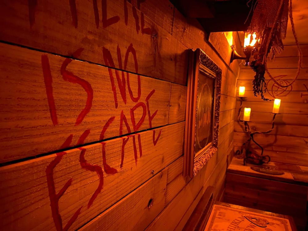 "A red lit cabin with the words ""There is no escape"" written in blood on the wall."