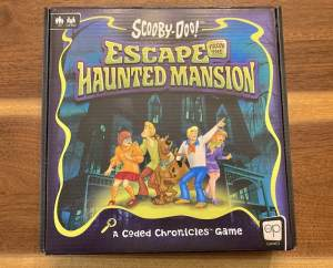 Scooby-Doo Escape from the Haunted Mansion box art depicts th Mystery Inc gang in front of an ominous mansion.