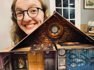 Lisa peering over the dollhouse.