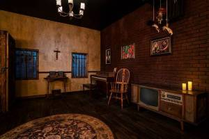 A creepy living room with an old tv/ radio and a cross hanging on the wall.