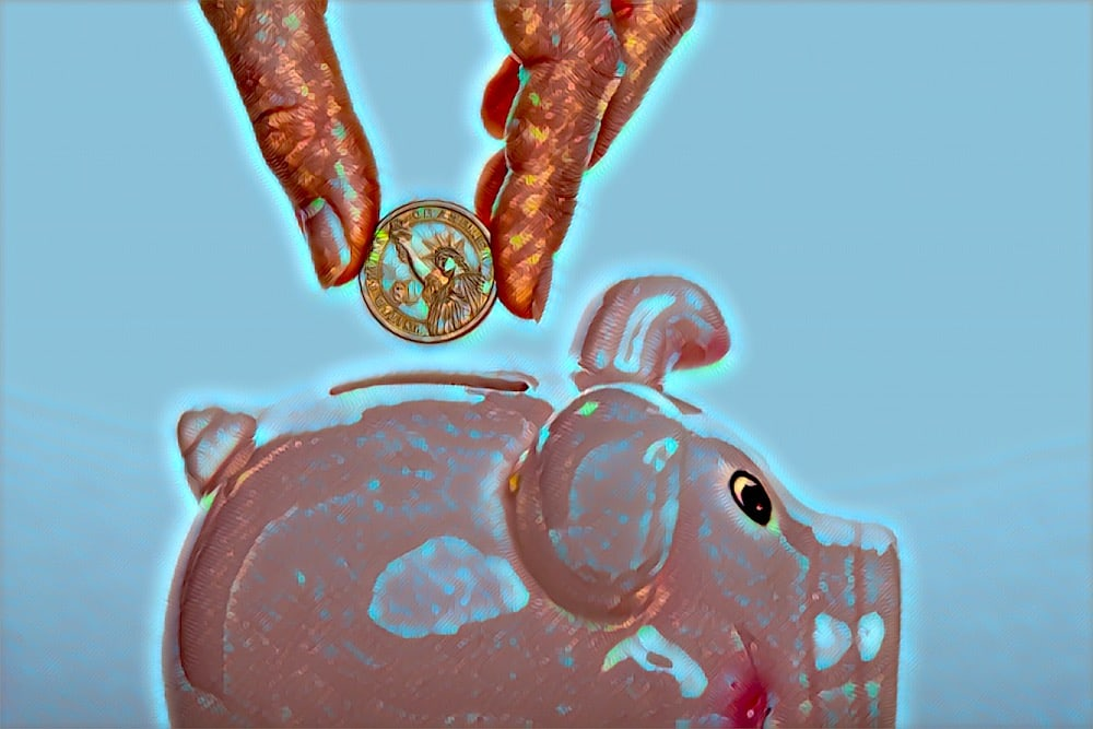 Glimmering fingrs placing a coin in a piggy bank.