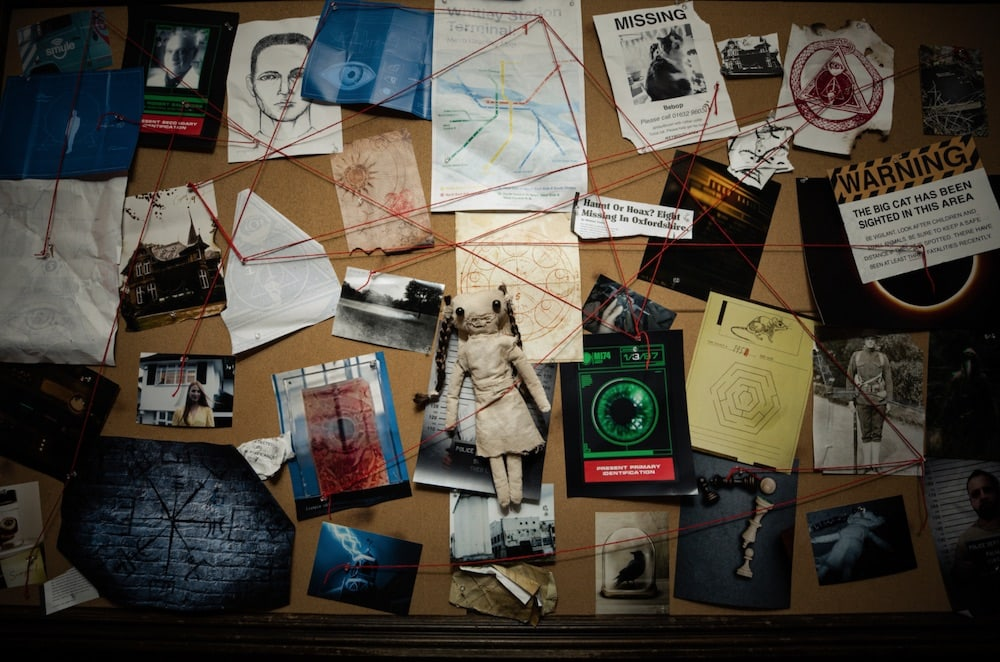 A bulletin board covered in documents, photos, and red string.
