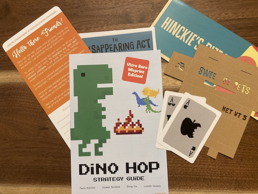 """Assorted componnts include a n 8 bit """"Dino Hop"""" strategy guide, unusual playing cards, a pizza menu, and some unusual flattened cardboard boxes."""