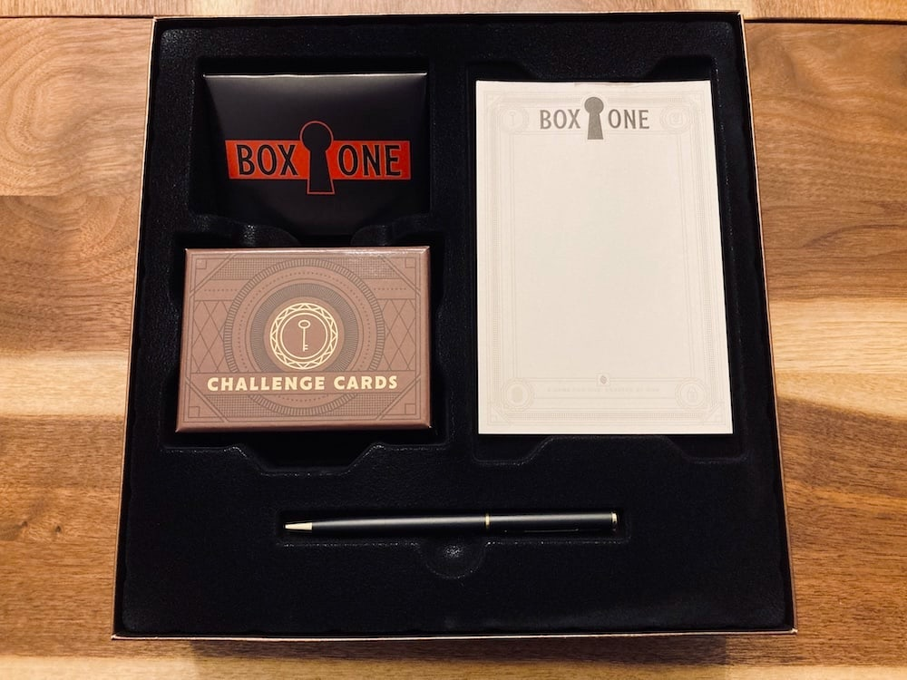 Box One open, a letter, pad, pen, and challnge cards cleanly displayed.