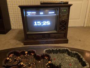 In-game: A 1980s living room with a D&D board, and a big old CRT television with an 8 bit video game style countdown clock.