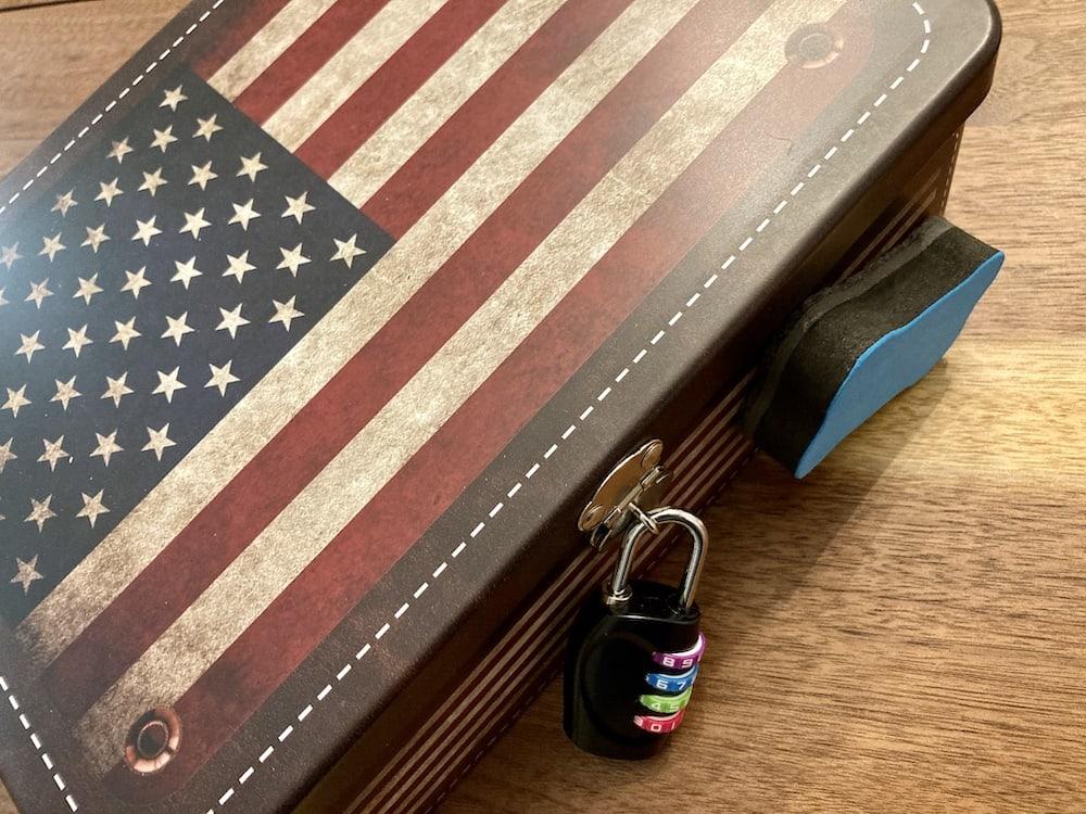 An American flag metal box with a padlock.