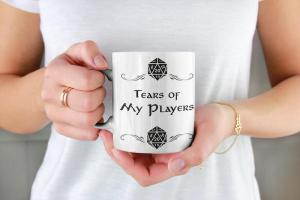 """Hands holding a much that depicts D20s and reads, """"Tears of My Players."""""""