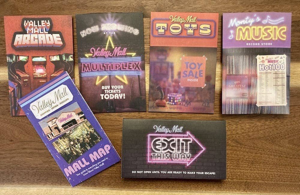 The Mall puzzle envelops featuring an arcade, multiplex, toy store, record store, mall map, and exit.
