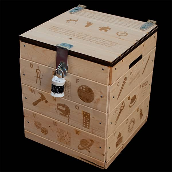 A large wooden crate with words, letters, and symbols laser etched on all of its faces. The crate is held shut by a 4 digit letter lock.
