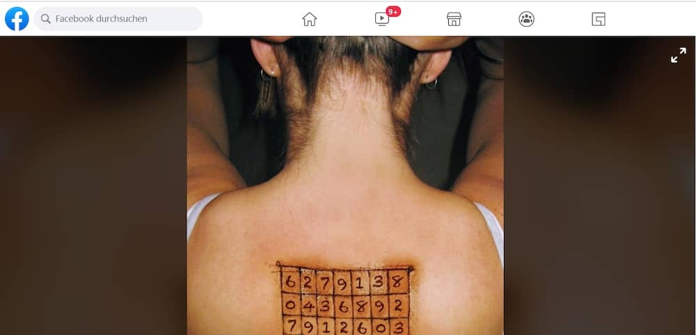 Image on Facebook of a woman from behind, a grid of numbers tattooed between her shoulder blades.
