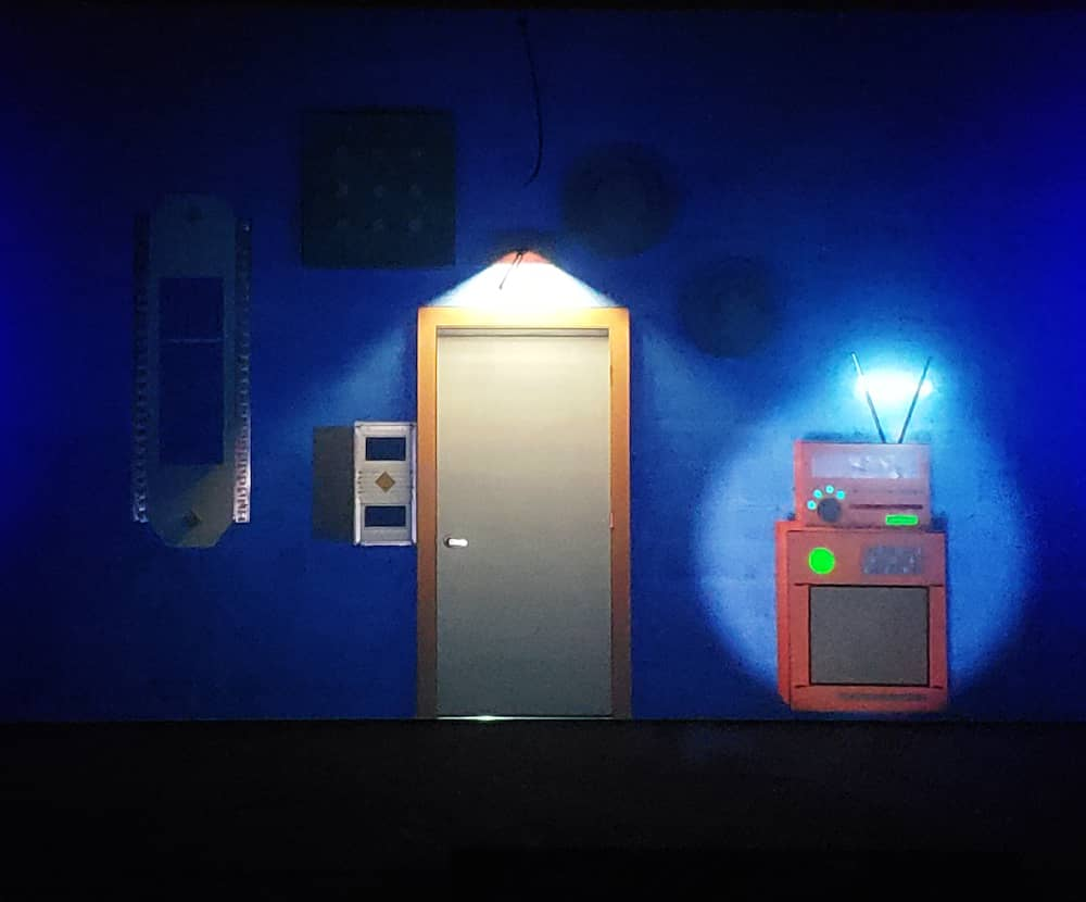 Projection of an escape room like environment. Includes a door and a mysterious technological contraption.