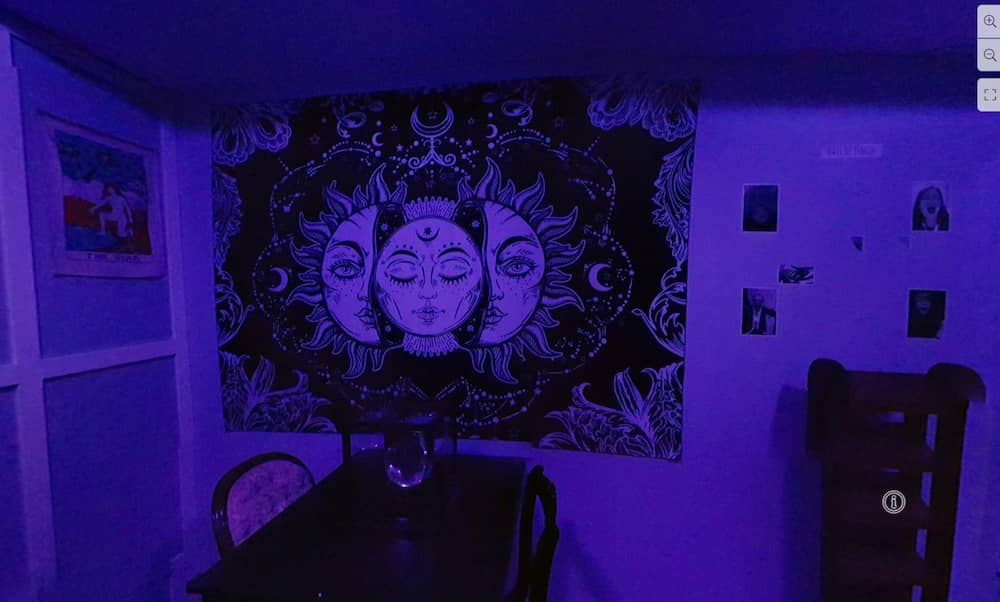 A purple lit room with mystical artwork hanging on the wall.