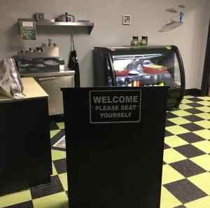 """In-game: View of a diner with a 60s UFO theme. In the center of the frame is a podium that says, """"Welcome. Please seat yourself."""""""