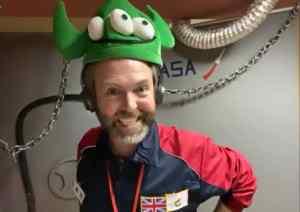 An astronaut wearing an alien hat.