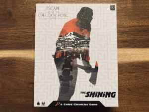 The Shining Escape From The Overlook Hotel game box, depicts a man wielding an axe with blood dripping from the blade.
