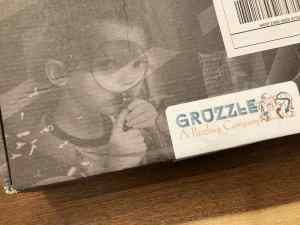 The Gruzzle box depicts a child looking through a magnifying glass.