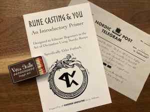 An open matchbox, a rune casting primer, and a nordic post telegram.