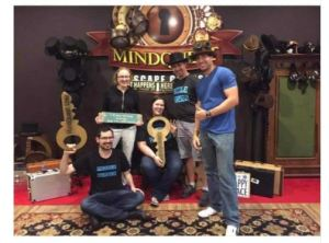 three men and 2 women are posing with giant prop keys in an escape room lobby