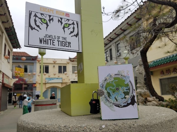 """A Chinatown plaza with a sign in the foreground reading """"Escape Room LA: Jewels of the White Tiger"""" above a small decorative box with a padlock."""