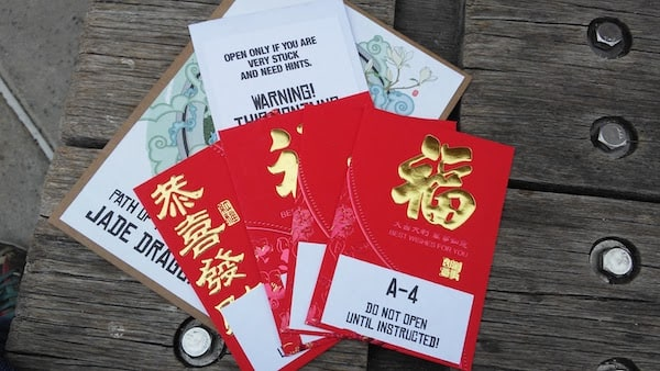 """Some papers on a park bench, with several red envelopes, the top one of which reads """"Do Not Open Until Instructed!"""""""