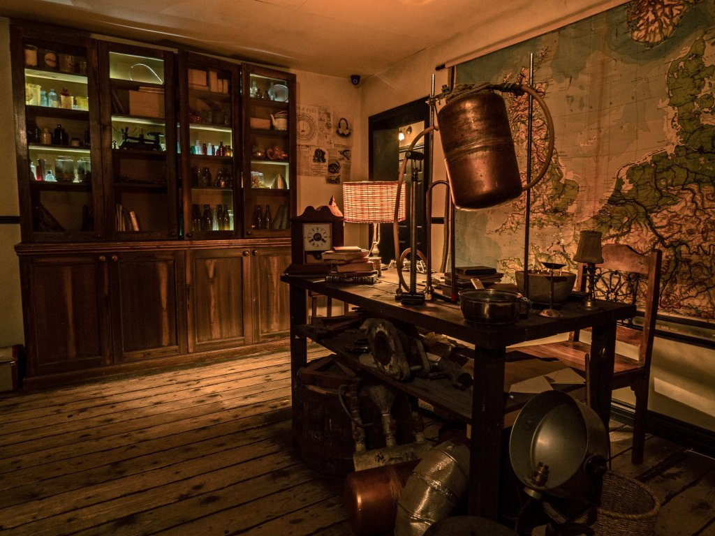 old timey looking room with a large map on the wall, bookcases and a table with scientific instruments
