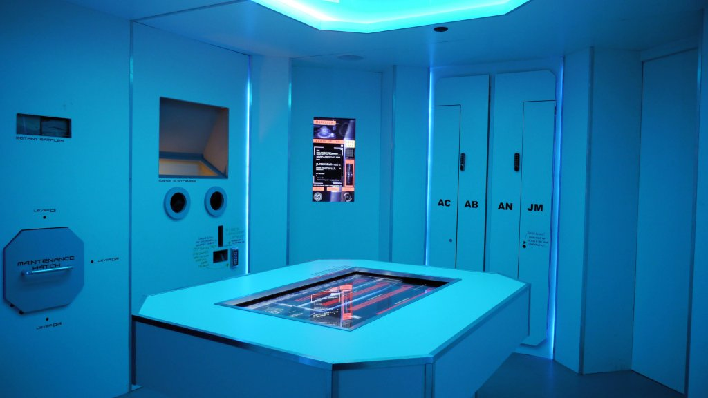 futuristic looking room, blue walls with monitors and screens on the walls