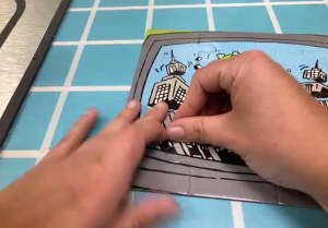Zoom view of a pair of hands assembling a jigsaw puzzle.