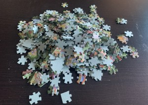 A pile of jigsaw puzzle pieces almost all of them have them same cuts.