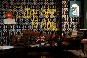 """Living room decorated like it's from the 1060's. The words """"the game is now"""" is spraypainted on the wallpaper."""