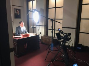 man being filmed with lights and camera sitting at a desk