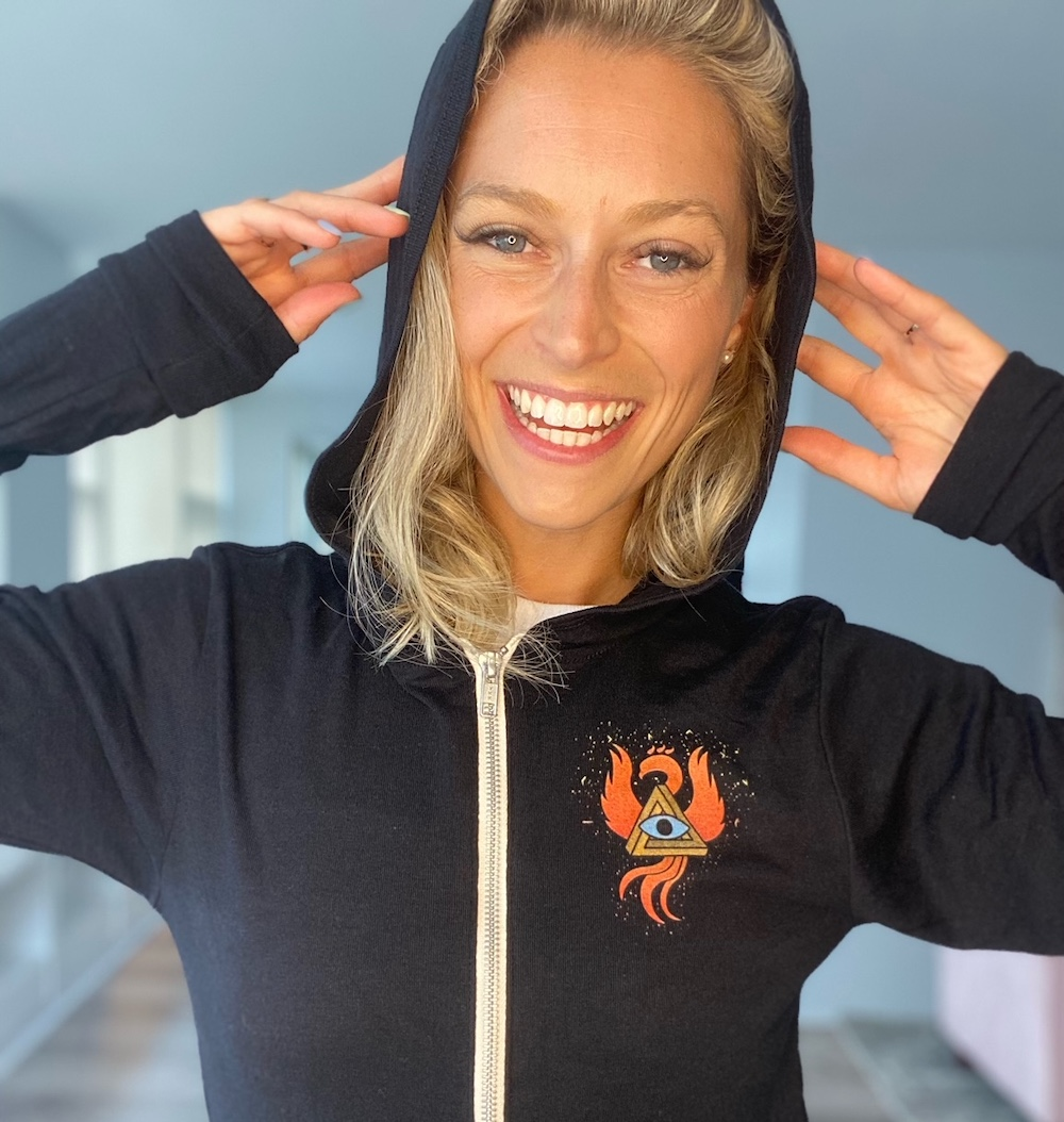 Woman wearing a black zipup hoodie with the RECON 21 phoenix and a hidden message.