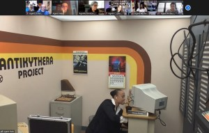 Someone kneeling by a computer desk in an 80s looking office space.