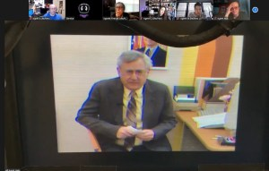 An older man sitting at a desk. It looks like a screenshot from grainy old video.
