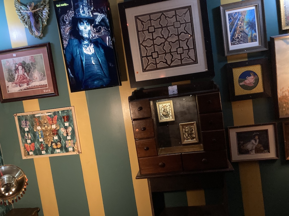 Assorted images hung on the wall of an old New Orleans curio shop.