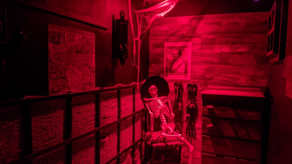 Captain's quarters on a pirate ship lit red. The skeleton of the captain rests wearing a fancy hat.