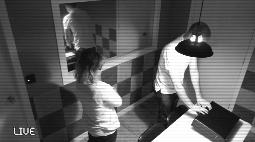Two people opening a briefcase in an interrogation room viewed through a black & white security camera.