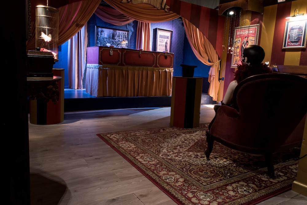 An intimate magician's stage surrounded by magical props and posters.