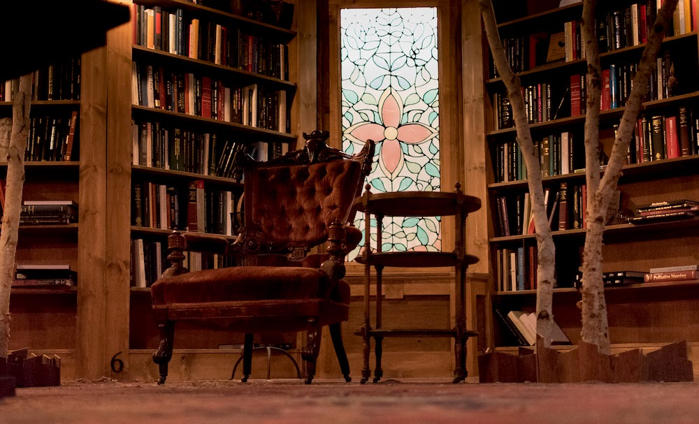 A large chair in the middle of a library study, surrounded by books.
