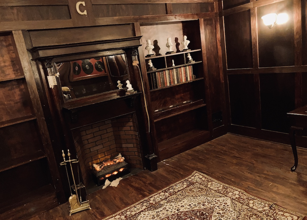 In-room: a bookshelf and fireplace in a study.
