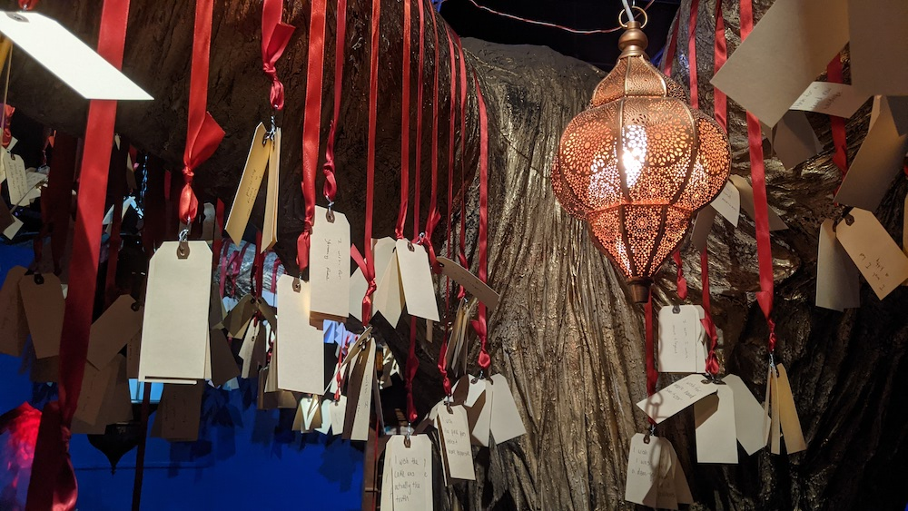 Closeup of a large object with many red ribbons and tags hanging from it, illuminated by an ornate lantern.