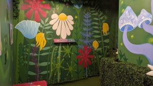 Painted forrest set with bright flowers, mushrooms, and a control panel with glowing buttons of various colors.